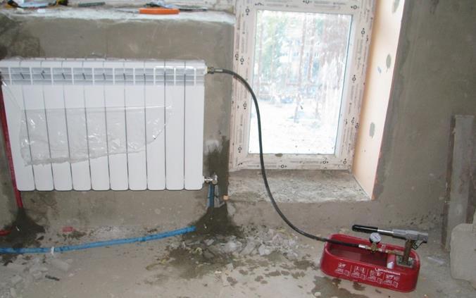 Фото: Опрессовка радиатора отопления с помощью специального прибора