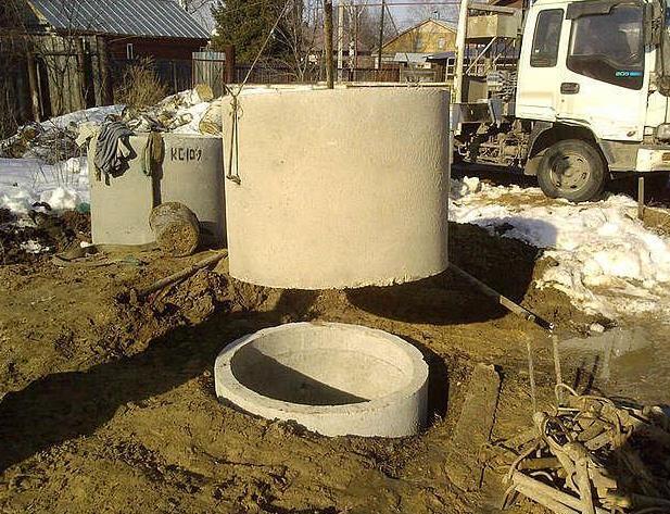 Фото: Процесс установки бетонных колец в яму